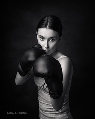 The Boxer - Black and White (saraghedina) Tags: boxinggloves tanktop darkbackground vertical oneperson fineart blackandwhite chiaroscuro strength boxer 50mm canon onelight studiolighting portrait woman