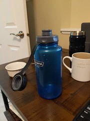 This is a test (photerlootestuser) Tags: waterbottle bottle blue ablendersittingnexttoacupofcoffee table indoors desk contemporary tableware plywood medicine plasticbottle black wooden diningtable shaker waterjug