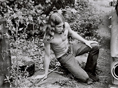 A young neighbor changing a flat tire, Ellicott City, Maryland, summer 1973 (A CASUAL PHOTGRAPHER) Tags: portraits men teenagers physiques hair hippies automobiles cars ellicottcity maryland howardcounty lugwrench