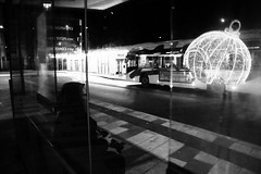 Attente... (Tonton Gilles) Tags: alençon normandie place du champ perrier mise en scène noir et blanc boule de noël illuminations bus alto gare déchange abribus passant passante assis voyageur reflets rue