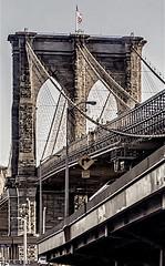 One of New York City's Most Famous Landmarks (nrhodesphotos(the_eye_of_the_moment)) Tags: dsc21843001084 wwwflickrcomphotostheeyeofthemoment theeyeofthemoment21gmailcom brooklynbridge suspensionbridge manhattan nyc stone metal cables outdoors americanflag outdoorscene roadway arc landmark texture stonework streetlights famous monochrome urban blackandwhite bridges signs roadsigns newyorkcity