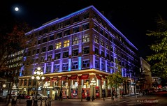 Historical Gastown by Light (Christie : Colour & Light Collection) Tags: gastown vancouver waterstreet lights lighting history 1800s 1870 windows streetview vancouverbc canada purple leckiebuilding britishcolumbia canadianhistory canadahistory vancouverhistory turnofthecentury historical settlement downtown downtownvancouver nightlights nightlighting edwardian edwardianerawarehouse warehouse factory historicdistrictofgastown 1908 street lowlighting nikkor nikon flickr flickrphotography moon streetlight lamplight vancouvereastside thecolourpurple storefront streetphotography cobblestone cambiestreetvancouver historicdistrict oldbuilding metrovancouver lowlightphotography nightphotography edwardianera