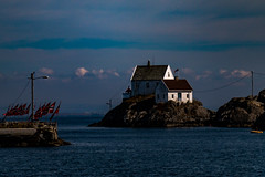 Flags and Lights (langdon10) Tags: karmøy northsea norway skudeneshavn water clouds flags house lighthouse rock shoreline
