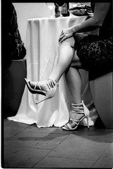 RachelSalWedding_033 (Johnny Martyr) Tags: legs shoes calves ankles woman her she detail close up black white film 35mm grain kodak hc110 sharp contrast muscular muscle athletic heels pumps strappy straps manual candid trix 1600 push process available light existing wedding documentary table sitting seated crossed crosslegged cross knee hand gesture toes point pointed dress attire formal dressy vintagestyle vintage style