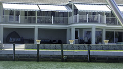 Living in Comfort by the Sea (soniaadammurray - On & Off) Tags: digitalphotography architecture water sea dock wall grass benches lights fence balcony windows terrace awnings reflections shadows boating exterior hbm artchallenge benchmonday