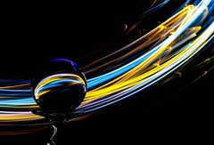 Earth Tones (Karen_Chappell) Tags: led glow black colour color colours colors colourful lights light ball round circle glass refraction orb sphere stilllife longexposure lightpainting blue orange yellow multicoloured lines curves