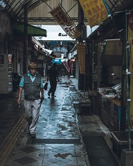 Rainy day (noel_street) Tags: tones naha wetground xt3 color alleys okinawa japan moody fujifilm rainyday desaturates walking people hat blue calle street streetphotography