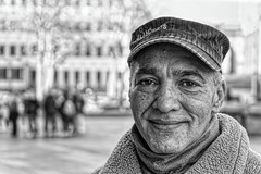 PORTRAIT OF A HOMELESS MAN (NorbertPeter) Tags: man street people cologne köln germany portrait spontaneous outdoor city urban streetphotography streetportrait sony ilce7 homeless poverty blackandwhite bw monochrome cap smile