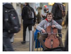 Playing the cello in a crowd (AurelioZen) Tags: europe netherlands utrecht railwaystationcourt busker cello streetmusician passersby
