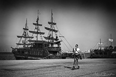 Chloe And The Pirates (Alfred Grupstra) Tags: ships pirates scooter woman greece blackandwhite nauticalvessel sailingship sea ship people oldfashioned history retrostyled travel cultures passengership sailing transportation harbor old militaryship outdoors sail