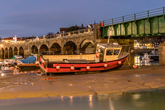 Stuck on the mud at night (wells117) Tags: folkstone uk arches boat bridge building cabin evening floats grounded house kent lifebouy lights lowtide mast nopeople outdoors outside railings reflections ropes sea sky structure stuck water windows