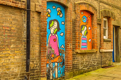 Old graffiti (wells117) Tags: folkstone uk arch backstreet bees bricks brickwork colourful daytime doorway girl graffiti kent lady nopeople outddors outdside paint path pavement pipe street streetview view wall wellworn window worn