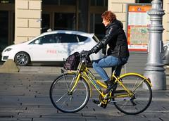 bike sharing (archgionni) Tags: donna woman bici bike street strada giallo yellow bleujeans luce ombre light shadows palo lamp torino italy