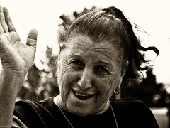 Welcome (Neil. Moralee) Tags: neilmoralee woman lady female old mature wave face portrait teeth dental cyprus pafos paphos smile cheerful happy bar owner cafe black white mono monochrome blackandwhite blackwhite neil moralee bw toned tones sepia candid olympus omd em5 joy wrinkles