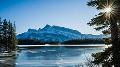 Mount Rundle as seen from Two Jack Lake (The Bear Den Photography) Tags: pentaxk1markii sunflare landscape rockymountains improvementdistrictno9 mountains snowcappedmountains unpavedroadphotography pentaxhdpentaxdfa28105mmf3556eddcwr 16x9 ishootraw roadtrip roadslesstravelled alberta elevation2948m9672ft park established1885 november2019 frozen mountrundle twojacklake reflection havecamerawilltravel naturallightphotographer lake fall gravelroadphotography snow trees clearbluesky ice parcnationalbanff thebeardenphotography thebearden sky canada banffnationalpark 2019 nostalgia alberta2019 wildrosecountry strongandfree