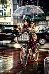 The stylish cyclist (Piotr_Lewandowski) Tags: shinjuku tokyo japan nippon asia japanese girl woman cycling bike cycle stylish candid mobile umbrella urbanite urban street streetphotography night nightlights nightshot rain dark person people
