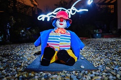 Clown (Colin Kavanagh) Tags: clown toy darkness arklow portrait toyportrait outdoors backgarden garden gardenphotography lighttrail lights lightrays lightandshadow colourful night nighttime nightphoto longexposure stones joker clowingaround hat torchlight