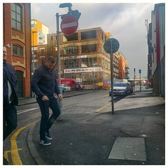 """""""Do you like my new trainers then or what?"""" (joanneharlow70) Tags: manchester people street men walking trainers jacket jeans roadmarkings road sidewalk pavement sinage buildings vehicles van derelict cars windows glass sky clouds daytime"""