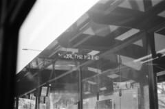 transit (monochrome) (nikku_neko) Tags: ilfordhp5 ilford monochrome 35mm film busstop buswindows bus transit reflections