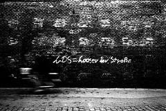 LDS (Ricoh GR1) (stefankamert) Tags: film analog analogue wall lds freising motionblur blur textures street stefankamert noir noiretblanc blackandwhite blackwhite ricoh grain gr gr1 ricohgr1 wideangle highcontrast cyclist blurry kodak trix 122019