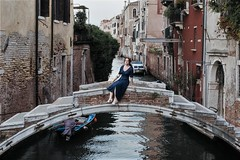 Don't do it! (markfly1) Tags: woman posing jumping candid street image venice italy europe lady girl blue dress pastel coloured buildings water canal boats red orange umber plaster brick stone trees bush ripples waterway gondola windows walls houses city scene