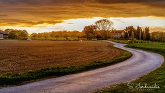 Following the Sunset (Stathis Iordanidis) Tags: dramaticsunset dramaticclouds farmland road path countryside nature amazinglandscape colorfulsky curves