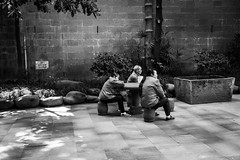 Cinema (Go-tea 郭天) Tags: chongqing républiquepopulairedechine cinema table chairs seated seats seating captivated group team old women ladies man workers break duty uniform together friends colleagues pavement acient history historical historic tradition traditional building construction yard rocks plants trees wall sun sunny shadow street urban city outside outdoor people candid bw bnw black white blackwhite blackandwhite monochrome naturallight natural light asia asian china chinese canon eos 100d 24mm prime