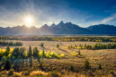 Teton View - Textured HDR (byron bauer) Tags: byronbauer grandtetons hdr highdynamicrange landscape field plain grass trees mountains sky clouds sun sunset texture painterly nationalpark wyoming topaz impression restyle rays fall blue