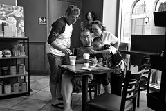 Center Of Attention (Rick Del Carmen) Tags: monochrome blackwhite coffeshop people cellphone chairstables restroom streetphotography fujifilmx70