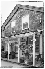Shoot The Breeze (maureen.elliott) Tags: blackandwhite architecture architecturaldesign architecturaldetails village structure porch chairs nostalgia