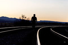 Into the Sunset (_aires_) Tags: grants newmexico unitedstatesofamerica aires iris tracks railroadtracks railway sunset man walking portrait silhouette canoneos5dmarkiv canonef28mmf18usm