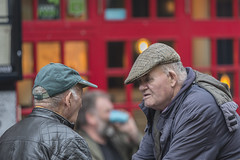 Exchanging views: Cap to Cap (Frank Fullard) Tags: frankfullard fullard candid street portrait cap conversation face talking red galway color colour irish ireland gossip