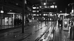 Wet Night 03 (byronv2) Tags: blackandwhite blackwhite bw monochrome street candid peoplewatching haymarket winter rain raining wet night nuit nacht edinburgh edinburghbynight edimbourg scotland westend tram publictransport platform commuter commuting commute