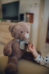 Young girl feeding teddy bear in living room (shixart1985) Tags: toy cute little teddy bear brown childhood lonely play day simple simplicity sitting waiting white home child adorable bar care casual comfortable concentrated copy space counter cozy daughter daytime feed funny interior kid kitchen pink playful serious soft spoon toddler