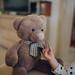 Young girl feeding teddy bear in living room