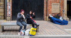 Castleford 016 (Peter.Bartlett) Tags: bag eating women unitedkingdom bench people streetphotography olympuspenf westyorkshire colour peterbartlett urban uk m43 microfourthirds eyecontact sitting men castleford england