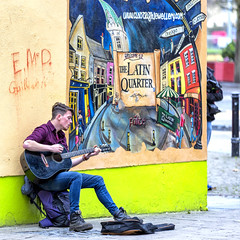 Busking in the Latin Quarter (Frank Fullard) Tags: frankfullard fullard candid street portrait color colour latinquarter mural art streetaret guitar music musician busker busking irish ireland square artist