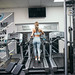Young blonde woman running on a treadmill in the gym