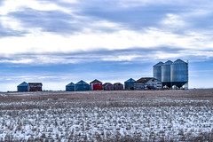 Crop fields and bins old and new (darletts56) Tags: sky blue cloud clouds white snow crop crops field fields prairie country countryside gray grey steel wood bin bins red paint farm farmer farmers brown grass grasses saskatchewan canada flat flatland land
