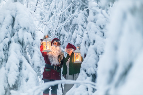 Santa Claus and his wife with candles in the snowy forest