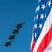 STACKED BLUE ANGELS FLYING BEHIND OLD GLORY