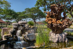 Wooden sculpture and water feature in Muang Boran in Samut Phrakan, Thailand (UweBKK (α 77 on )) Tags: muang mueang boran ancient city siam open air museum park garden bangkok samut phrakan thailand southeast asia sony alpha 77 slt dslr wood sculpture water feature waterfall