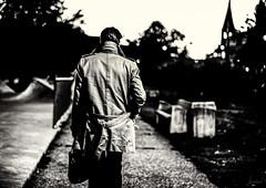 L'homme à la gabardine. (LACPIXEL) Tags: homme man hombre garbardine gabardina raincoat église collégiale church iglesia clocher arbre tree árbol rue street calle noiretblanc blancoynegro blackandwhite marcher andar walking walk sony flickr lacpixel