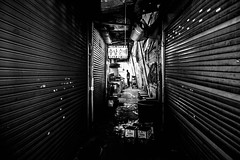 Dark commercial corridor (Phg Voyager) Tags: korean asia phgvoyager leica bw street city urban streetphotography shops contrast dark wet add logo fun light curtain stores narrow market buyeong incheon mp summilux 24mm silhouet