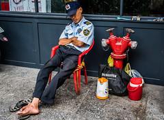2019 - Vietnam - Ho Chi Minh City - 16 - On Guard (Ted's photos - For Me & You) Tags: 2019 cropped hochiminhcity nikon nikond750 nikonfx saigon tedmcgrath tedsphotos vietnam vignetting shoeless guard securityguard firehydrant red redrule ballcap cap cooler jug sandals 1people hcmc