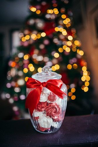 Jar with candy and a Christmas tree in the blurry background