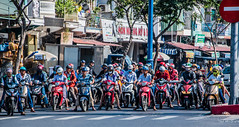2019 - Vietnam - Ho Chi Minh City - 29 - Motorcycle Mayhem (Ted's photos - Returns Early February) Tags: 2019 cropped hochiminhcity nikon nikond750 nikonfx saigon tedmcgrath tedsphotos vietnam vignetting motorcycle motorcycles streetscene street helmuts motorcyclehelmut riders masks facemasks wheels bikers bikes wideangle widescreen red redrule crosswalk hcmc