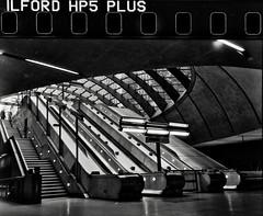 Canary Wharf (scarbrog) Tags: london canarywharf underground tube blackandwhite monochrome escalator scannedwithcamera affinityphoto affinityphotosoftware londondocklands canon7 canon7rangefinder canon50mmf18ltm hp5 ilfordhp5 ilfordfilm sprocketholes