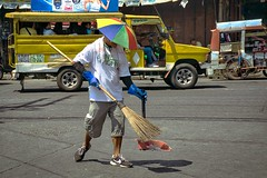 Clean sweep (Beegee49) Tags: people street man sweeping cleaning umbrella hat happy planet sony a6000 bacolod city philippines asia
