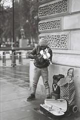 Street Performer (goodfella2459) Tags: nikonf4 afnikkor50mmf14dlens adoxsilvermax100 35mm blackandwhite film analog london city street musician streetperformer streetartist building bwfp